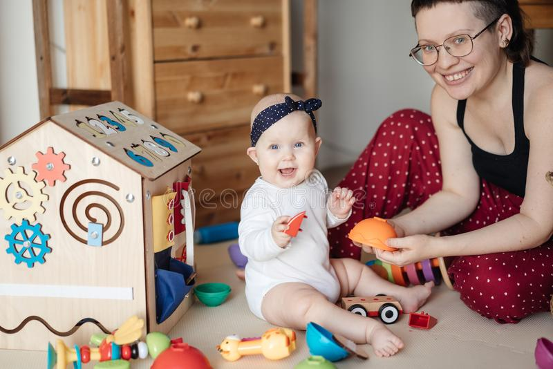 Cute baby plays with mom and rejoices. Family portrait Mom and Baby. stock photos