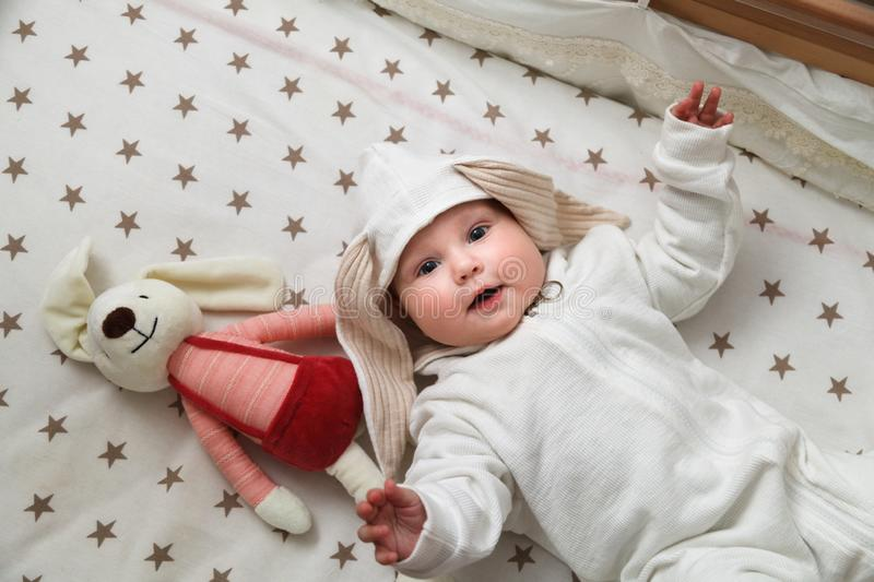 Cute baby in the rabbit costume lying in the bed with toy stock photos