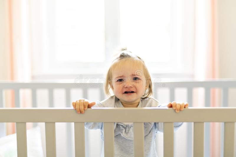 Cute baby baby on the baby room crib. A Baby on the baby room crib royalty free stock photography