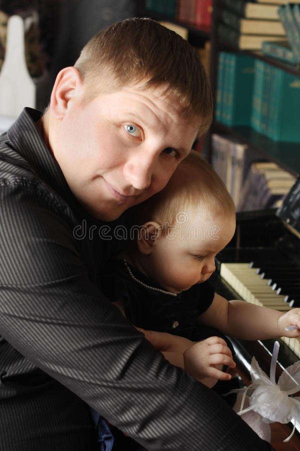 Download Cute Baby Sits At Knees Of Her Father And Touches Piano Stock Photo - Image: 32795728
