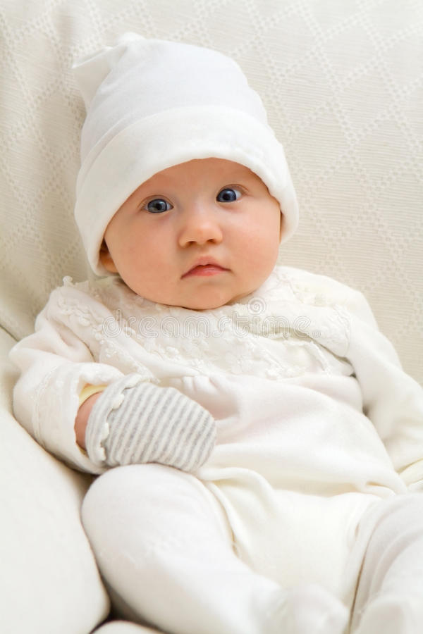 Cute Baby Sitting. Sweet baby sitting on couch wearing white royalty free stock images