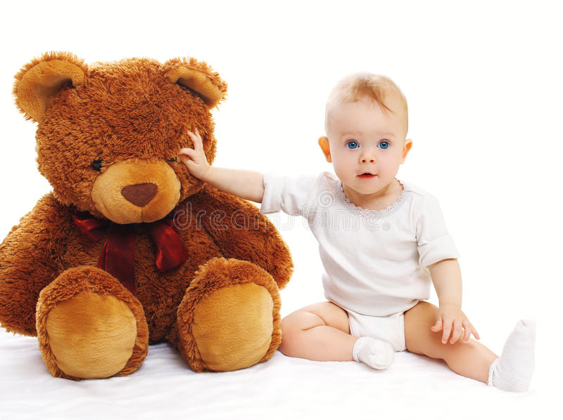 Cute baby sitting with big teddy bear on white. Background royalty free stock image