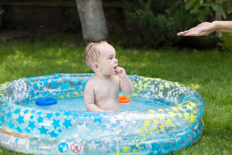 Cute baby sitting in outdoor swimming pool and looking at mother. Cute baby boy sitting in outdoor swimming pool and looking at mother stock photography