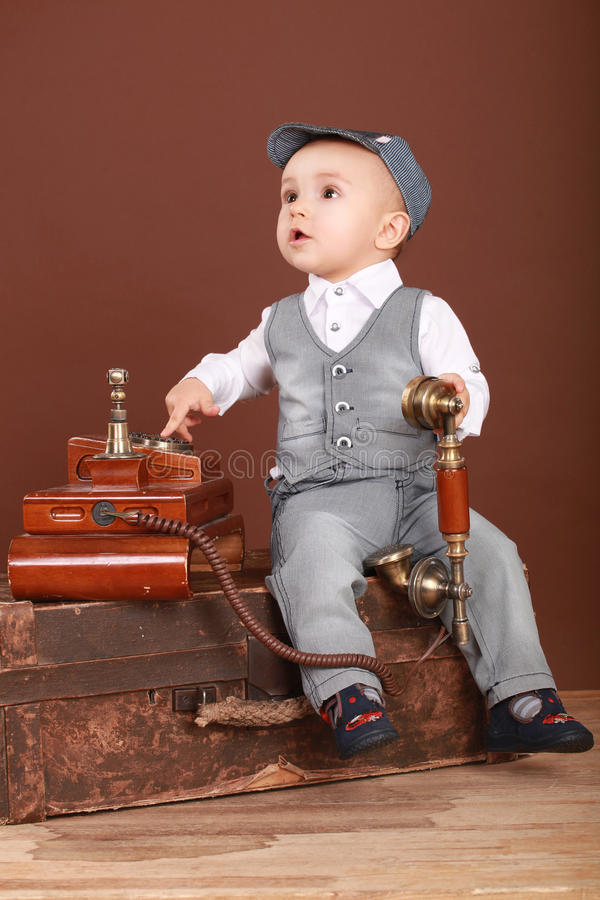 Cute baby sitting on a suitcase, holding a vintage phone royalty free stock photography
