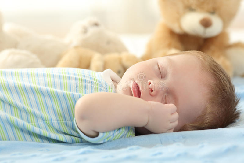 Cute baby sleeping on a bed royalty free stock photography