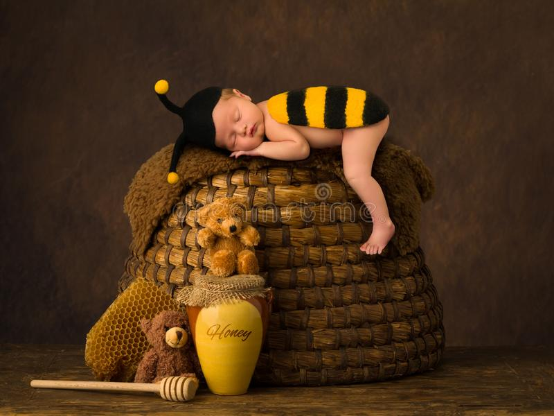 Cute baby sleeping on beehive. Cute baby sleeping in bee outfit on top of antique beehive royalty free stock photos
