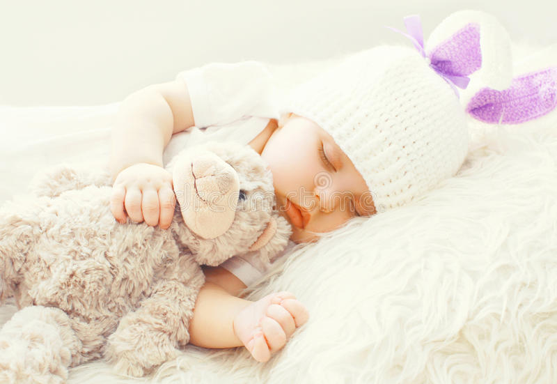 Cute baby sleeping with teddy bear toy on white soft bed royalty free stock photography