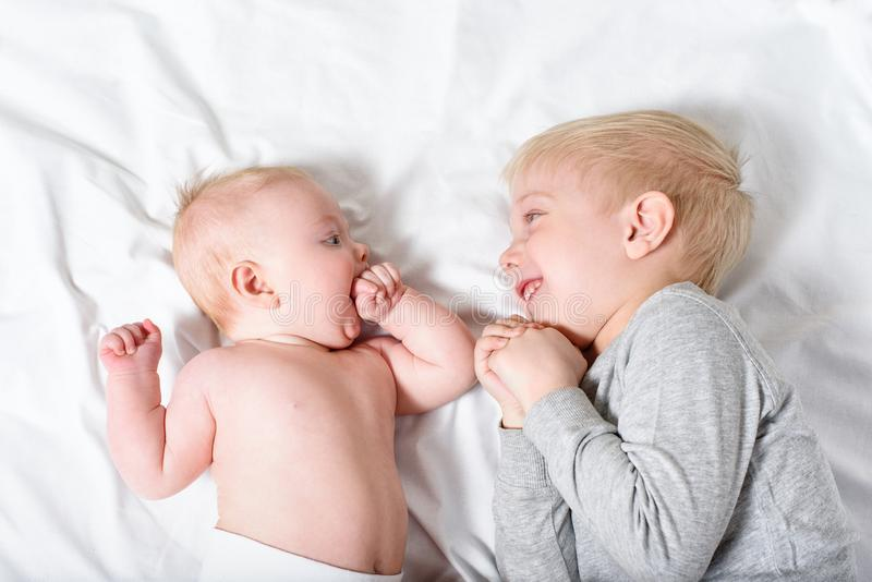 Cute baby and smiling older brother are lying on the bed. Play and interact. Top view stock photography