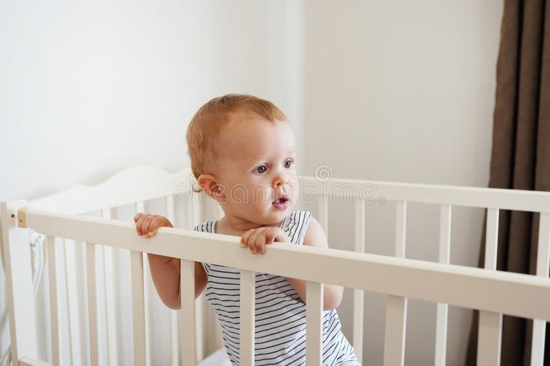 Cute baby standing in a white round bed. White nursery for children. Little girl learning to stand in his crib stock photography