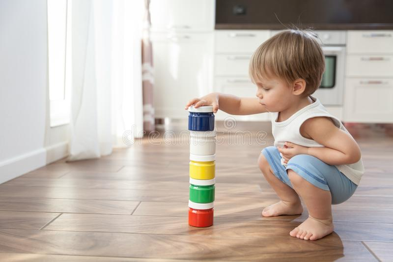A cute baby stands next to the paints in the cans. royalty free stock image