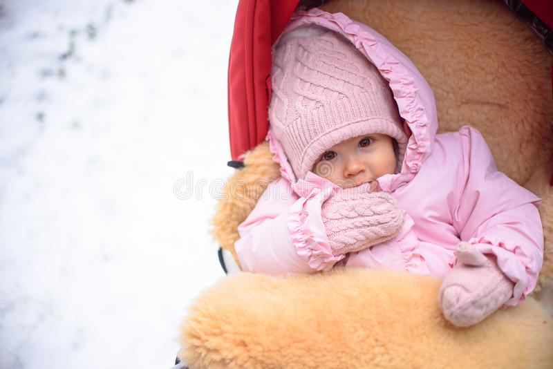 Cute baby in stroller on frosty winter day. Baby wearing woolen warm hat and mittens and lying in lama fur coated red stroller. 1 royalty free stock images