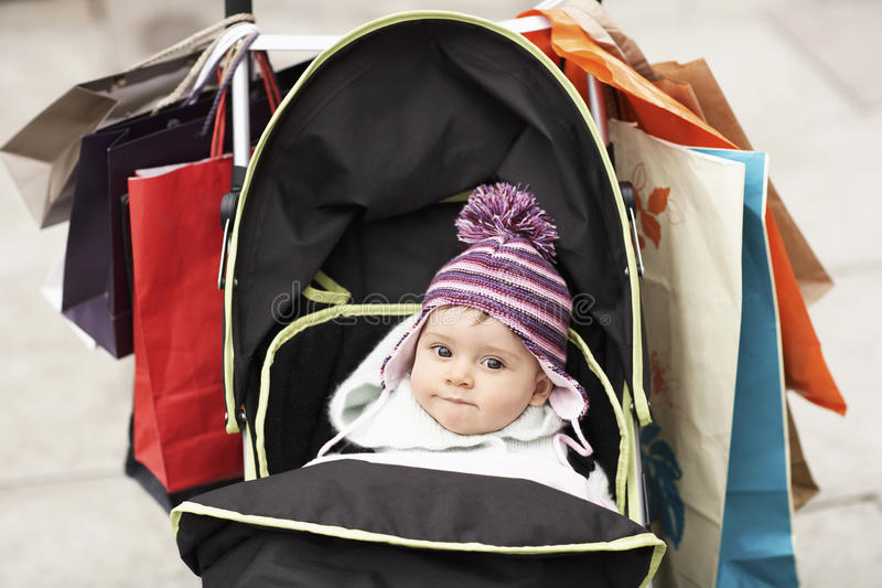 Cute Baby In Stroller Hung With Shopping Bags. Portrait of cute baby in stroller hung with shopping bags stock photos