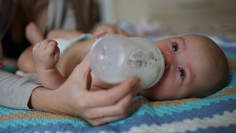 Cute baby sucks milk from a bottle. Feeding baby. Cute little baby is lying in a bed and sucks milk from a bottle. Feeding baby stock photo