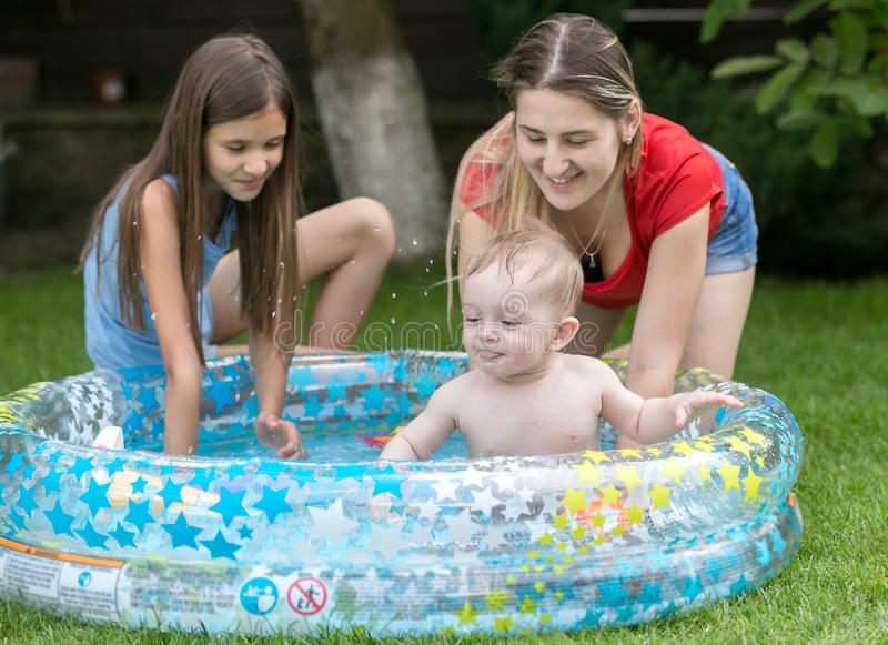 Cute baby swimming in outdoor pool with mother and elder sister. Cute baby boy swimming in outdoor pool with mother and elder sister royalty free stock photo