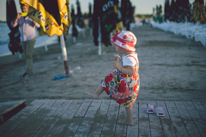 Cute baby toddler girl on the beach. Summer sunset on the beach royalty free stock images
