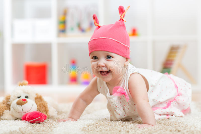 Cute baby with toy crawling on the floor stock images