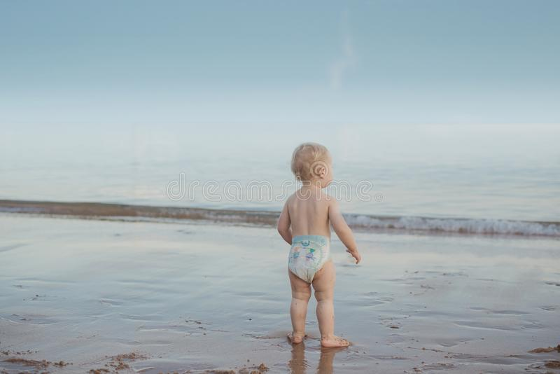 Cute baby watching an ocean`s wave stock photo