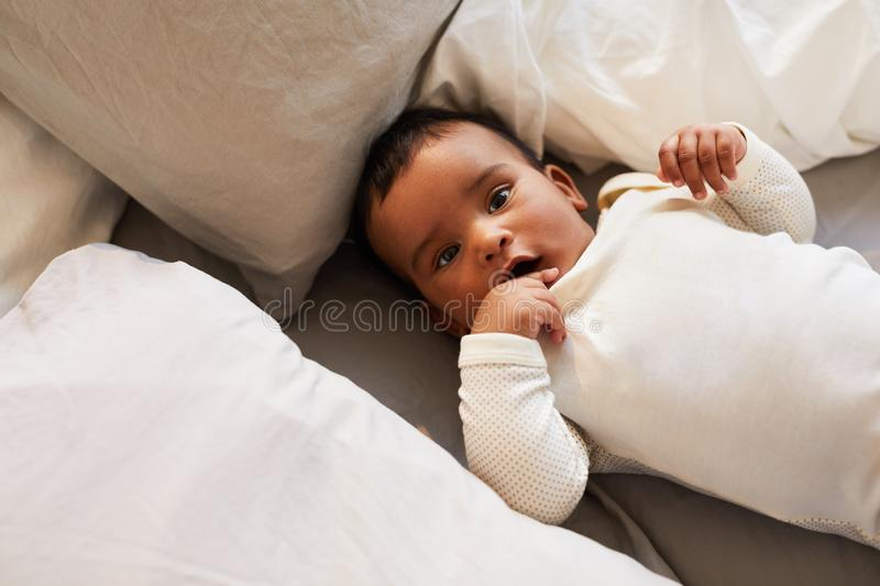Cute baby in white baby suit stock image