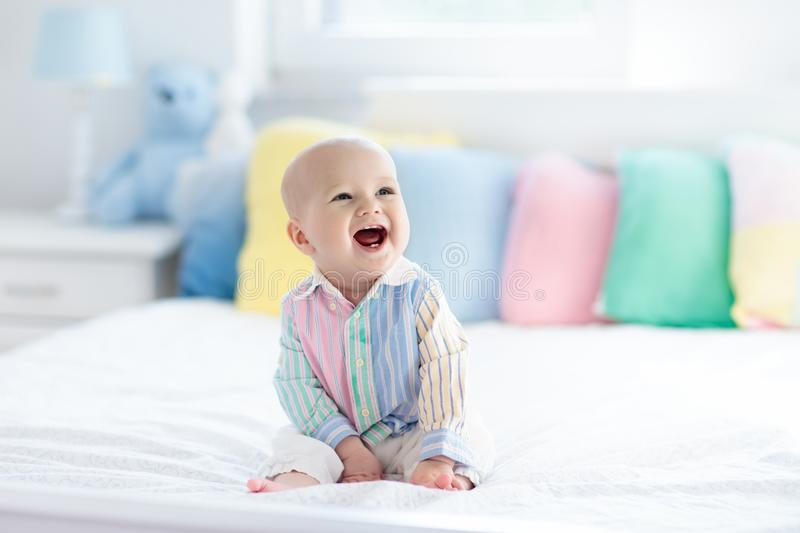 Cute baby on white bed royalty free stock image