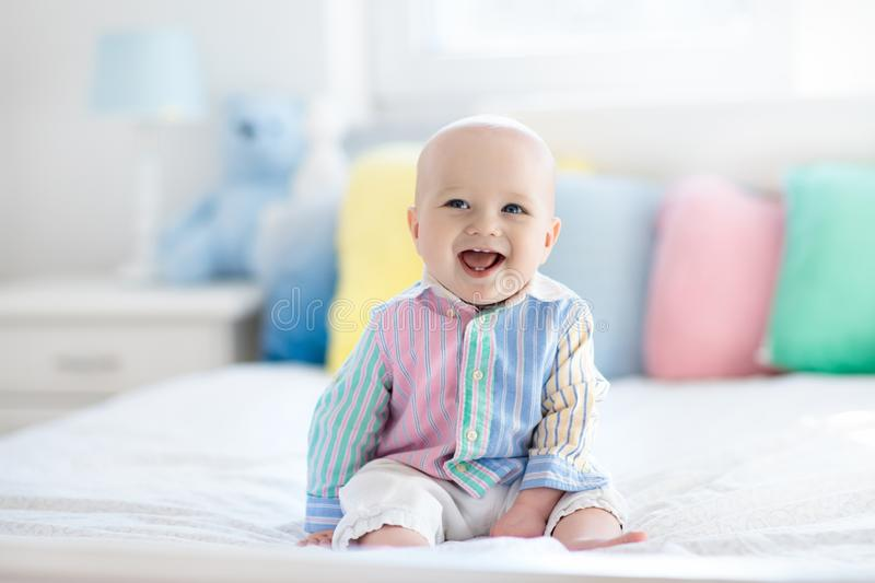 Cute baby on white bed. Baby boy in white bedroom. Newborn child in bed with pastel color cushions. Nursery for children. Textile, pillows and bedding for kids stock photo