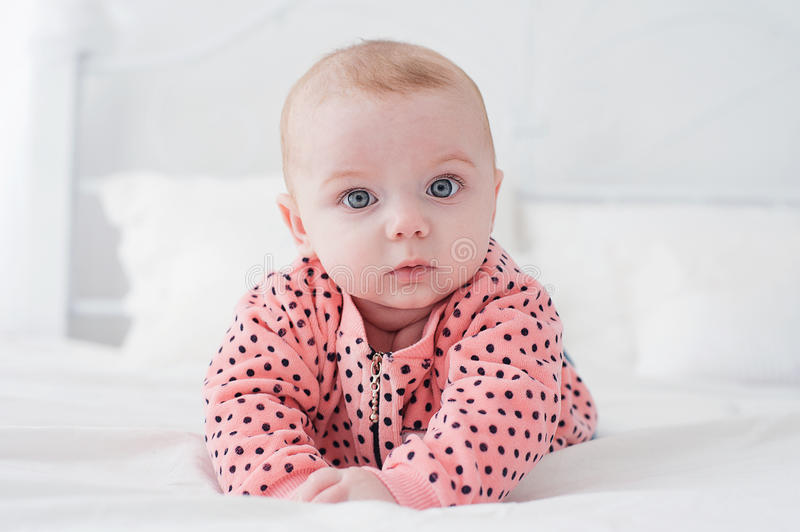 Cute baby on the white bed stock photo