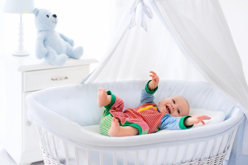Cute baby in white nursery. Funny baby in white crib with canopy. Nursery interior and bedding for kids. Laughing little boy playing in moses basket. Bedroom stock photos