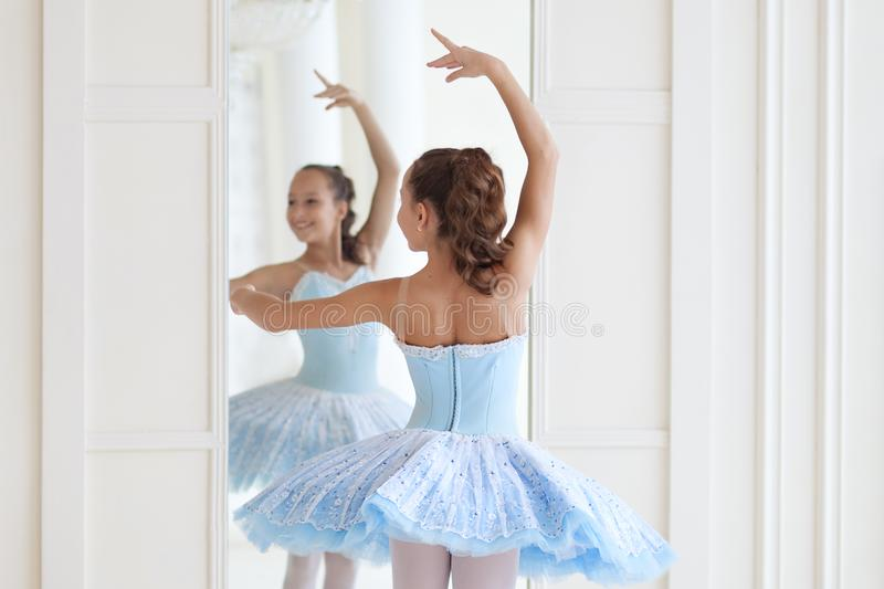 A cute ballerina in ballet costume and in pointe dances near the mirror. Girl in the dance class. The girl is studying ballet. Bal. Lerina is dancing. The dancer stock image