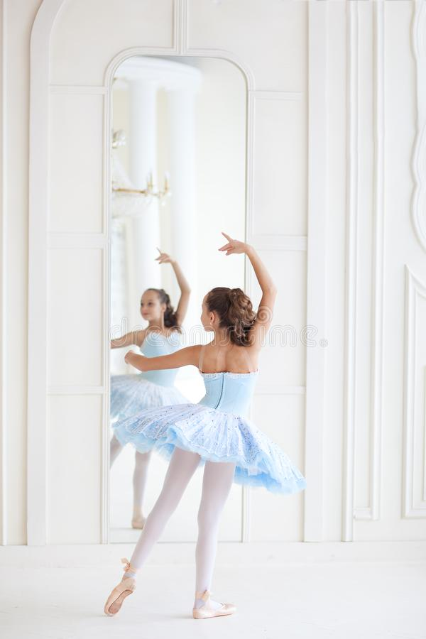 A cute ballerina in ballet costume and in pointe dances near the mirror. Girl in the dance class. The girl is studying ballet. Bal royalty free stock photo