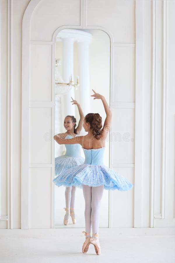 A cute ballerina in ballet costume and in pointe dances near the mirror. Girl in the dance class. The girl is studying ballet. Bal royalty free stock photography