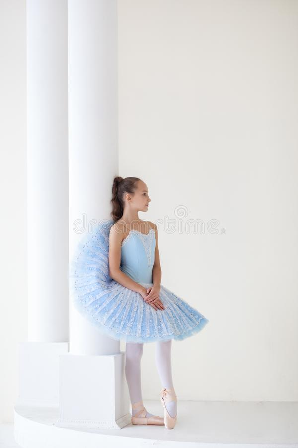 A cute ballerina in ballet costume and in pointe is dancing in a white studio. Girl in the dance class. The girl is studying balle stock photo