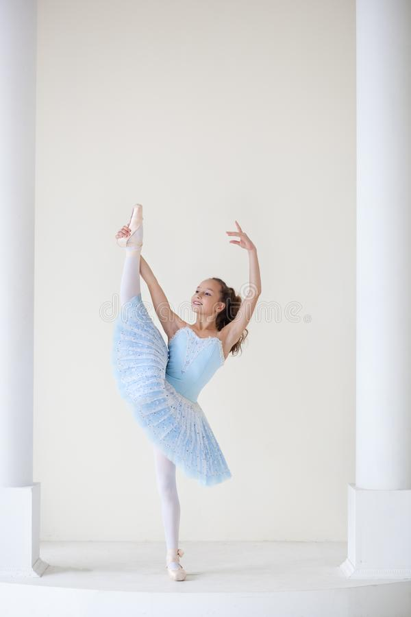 A cute ballerina in ballet costume and in pointe is dancing in a white studio. Girl in the dance class. The girl is studying balle stock images