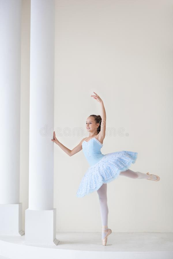 A cute ballerina in ballet costume and in pointe dances near the mirror. Girl in the dance class. The girl is studying ballet. Bal stock photo