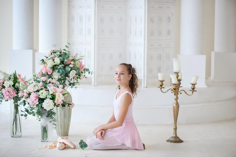 A cute ballerina in a ballet pink tutu and in poins sits on the floor. Girl in the dance class. The girl is studying ballet. Class stock photography