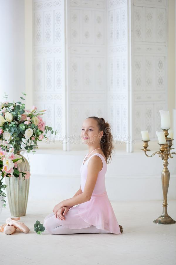 A cute ballerina in a ballet pink tutu and in poins sits on the floor. Girl in the dance class. The girl is studying ballet. Class royalty free stock image