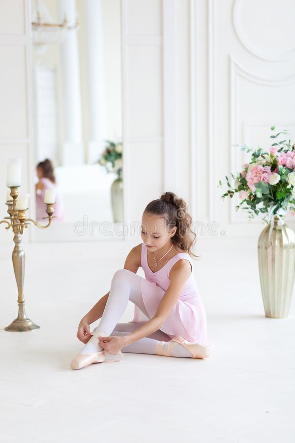 A cute ballerina in a pink ballet costume is sitting in a chair and tying pointe shoes.Girl in the dance class. The girl is studyi royalty free stock image