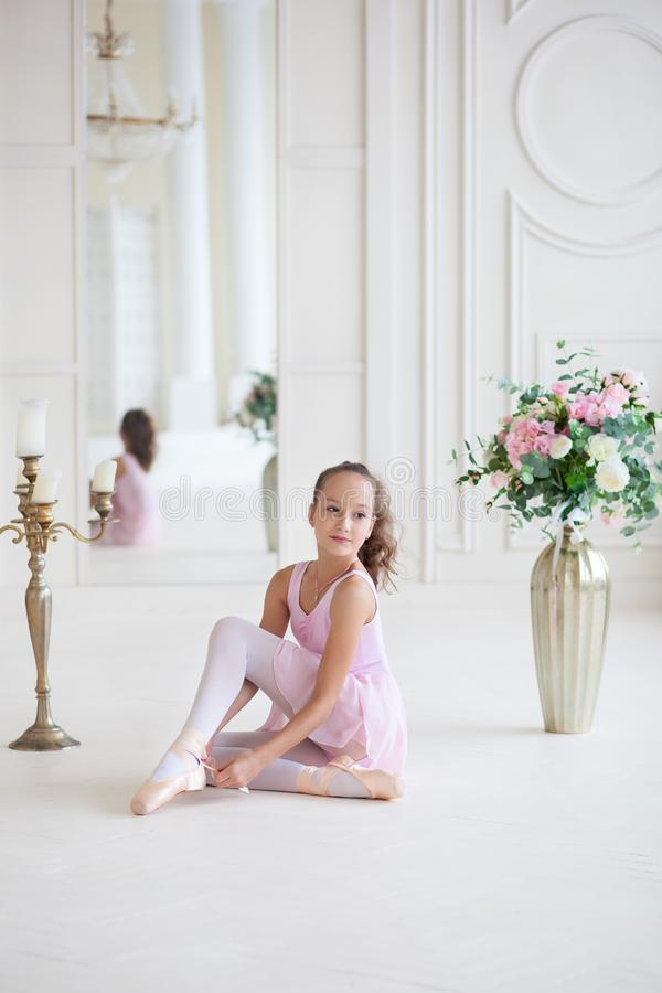 A cute  ballerina in a pink ballet costume is sitting on the floor and tying pointe shoes. Ballerina in the dance class.The girl i. S studying ballet. Ballerina stock photo