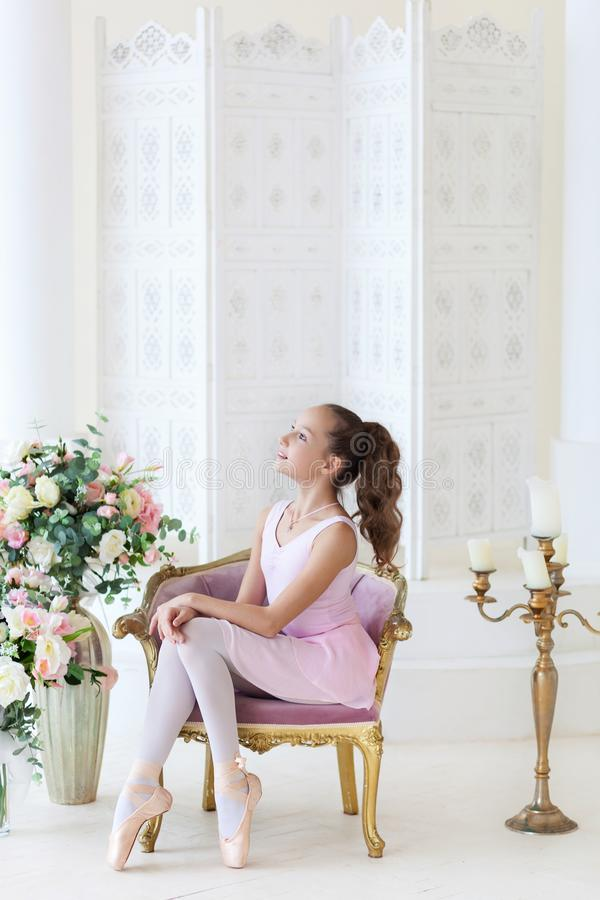 A cute ballerina in a pink tutu and in pointe sits in a chair. The girl is studying ballet. Ballerina dancing in a white studio. C royalty free stock photo