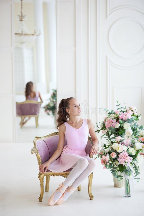 A cute ballerina in a pink tutu and in pointe sits in a chair. The girl is studying ballet. Ballerina dancing in a white studio. C stock images