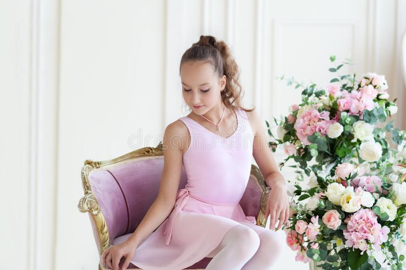 A cute ballerina in a pink tutu and in pointe sits in a chair. The girl is studying ballet. Ballerina dancing in a white studio. C stock photos