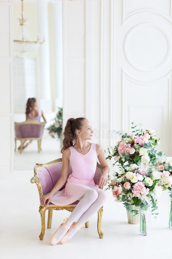 A cute ballerina in a pink tutu and in pointe sits in a chair. The girl is studying ballet. Ballerina dancing in a white studio. C. Lassical dance, ballet royalty free stock images