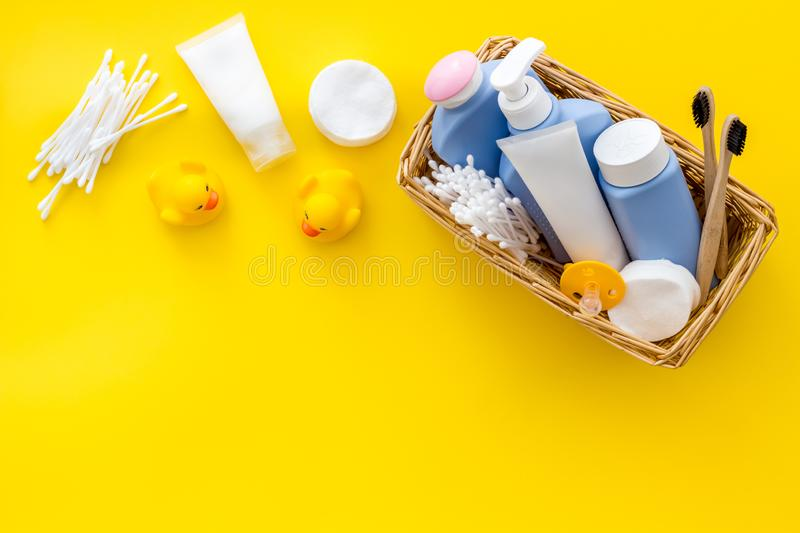 Cute bathroom cosmetics set with yellow rubber duck on yellow background top view pattern space for text. Cute bathroom cosmetics set with yellow rubber duck on stock image