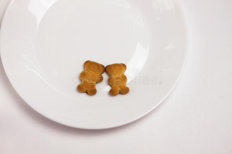 Cute bears cookies on the ceramic round plate  on white background. View from above, flat lay stock photography
