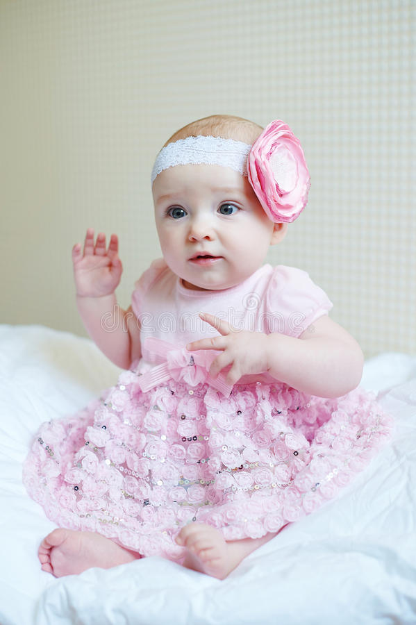 Cute beautiful baby girl sitting on a bed in pink dress stock photography