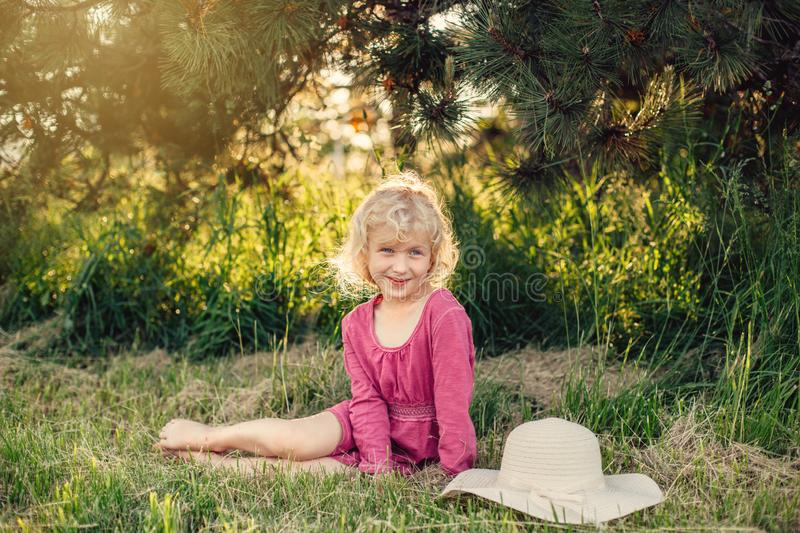 Cute beautiful blonde Caucasian girl in red pink dress with messy untidy hair sitting on ground grass in park outdoor at sunset. Portrait of cute beautiful stock image