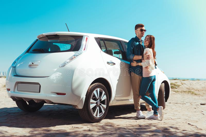 Cute beautiful couple coming to the beach on their white car. To the beach. Cute beautiful couple hugging each other while coming to the beach on their white car stock image