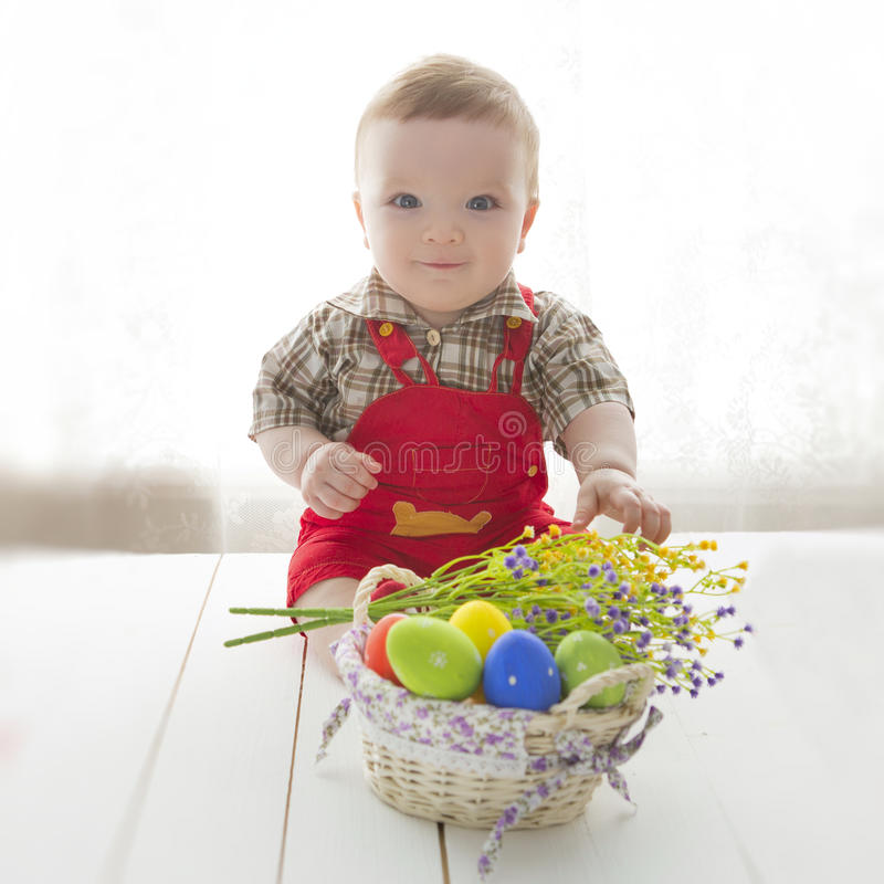 Cute beautiful emotional baby sitting with easter egg stock images