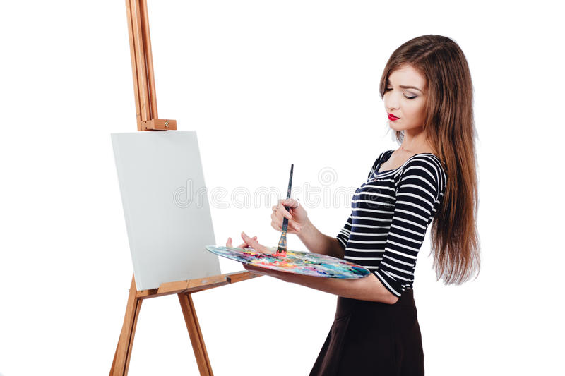 Cute beautiful girl artist painting a picture on canvas easel. Space for text. Studio white background, isolated. Cute beautiful girl artist painting a picture stock image