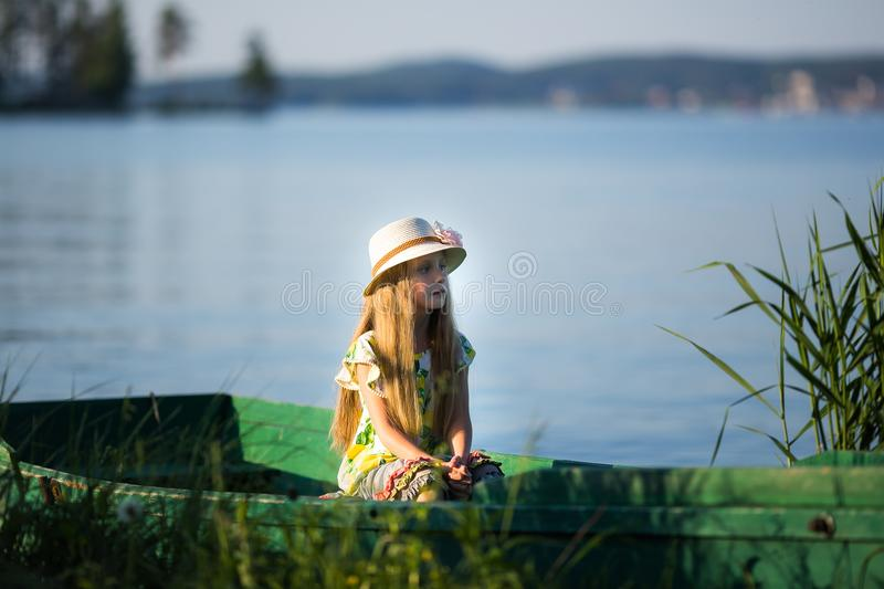 Cute beautiful girl sits in a boat on the lake stock photo