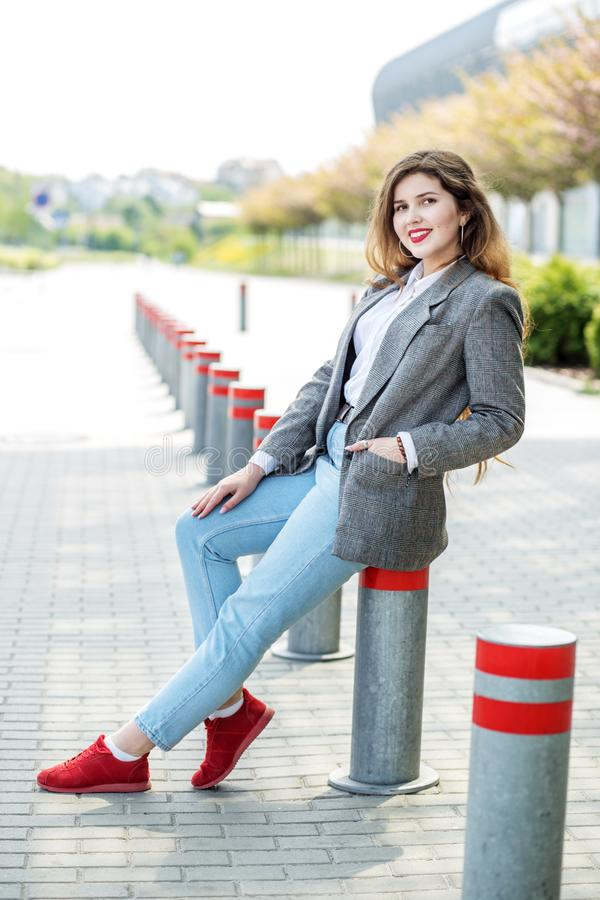 Cute beautiful girl sitting on the street. Concept of lifestyle, portrait, travel stock images