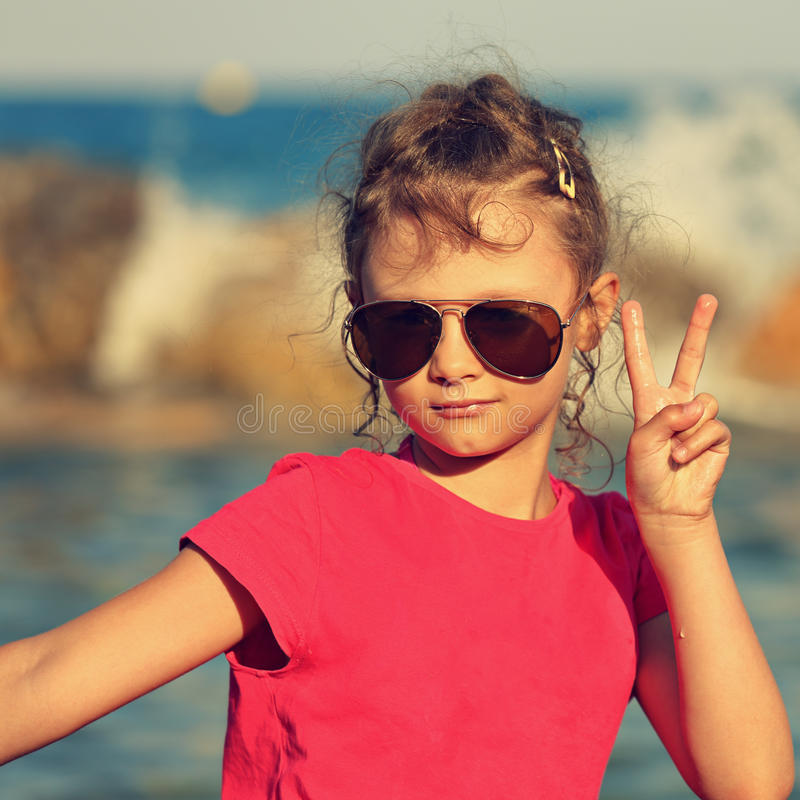 Cute beautiful kid girl in fashion sunglasses showing v sign making the selfie on blue sea and sky background. Toned closeup port royalty free stock photo
